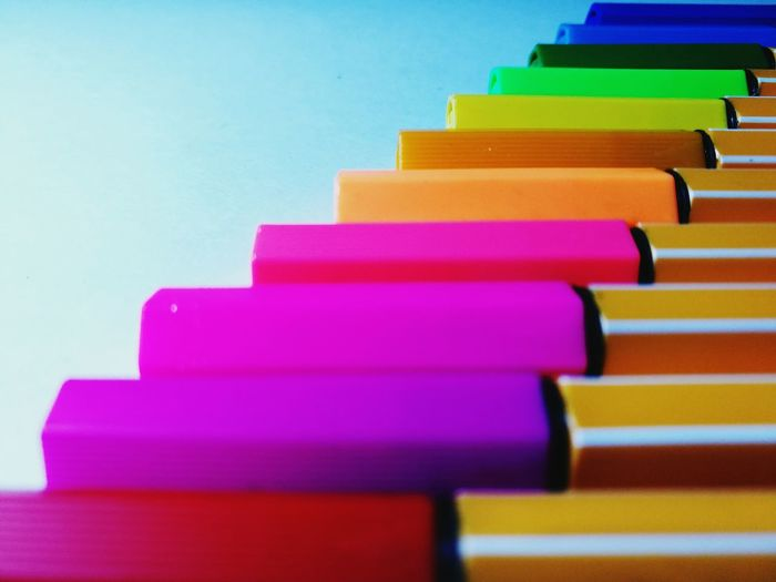 Close-up of colorful felt tip pen in row over colored background