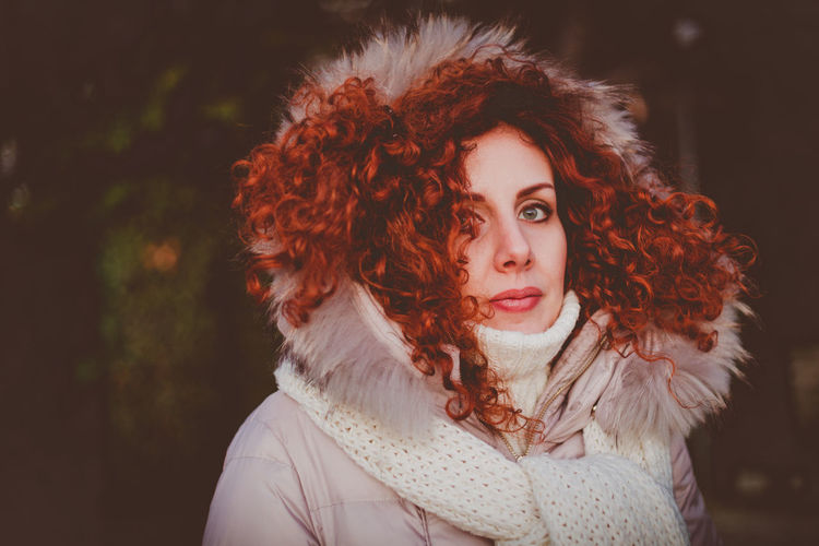 Close-Up Portrait Of Young Woman In Warm Clothing Outdoors