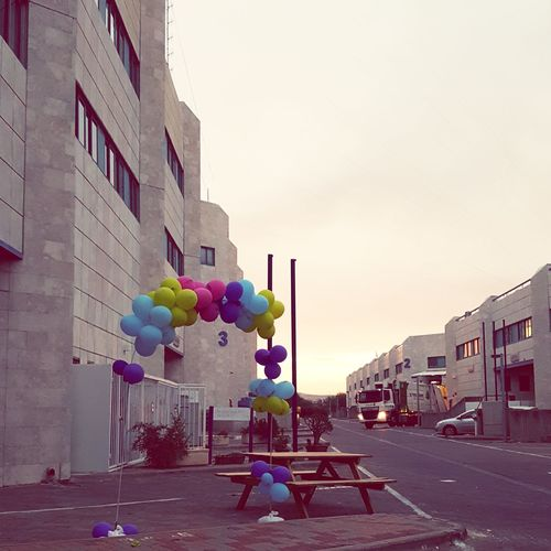 Multi colored balloons against buildings in city