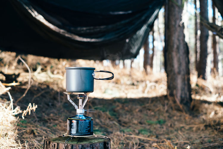Camping Camping Stove Close-up Coffee Coffee - Drink Cup Day Drink Field Focus On Foreground Forest Land Machinery Metal Nature No People Outdoors Plant Silver Colored Tree Tree Trunk Trunk