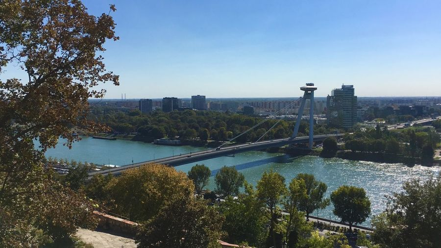 Scenic view of river by city against clear blue sky