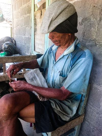 Senior man making cigarette while sitting on chair