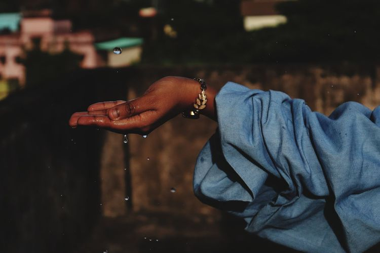 Cropped image of hand holding water at night