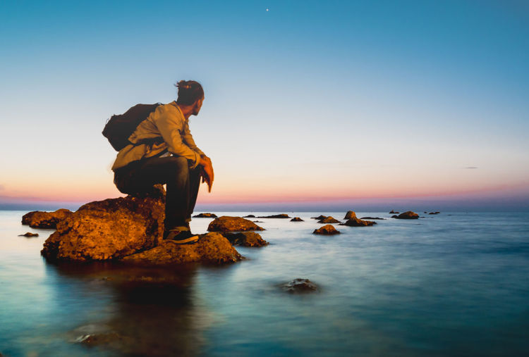Man sitting on rock by sea against sky during sunset