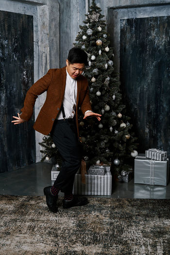Full length of young man standing by christmas tree