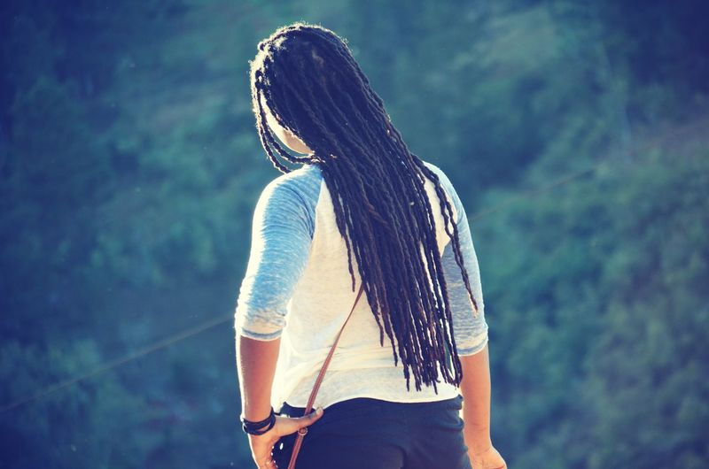 Rear view of young woman with dreadlocks standing outdoors
