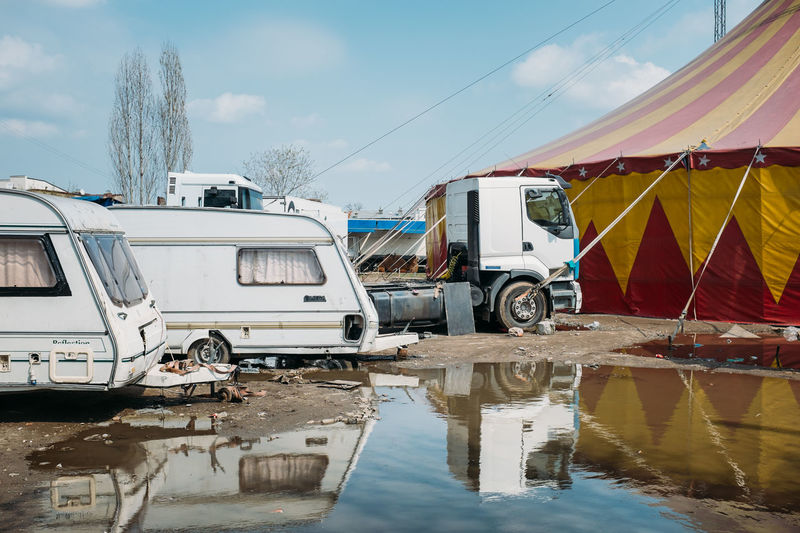 Side View Of Camper Vans Against Cropped Tent