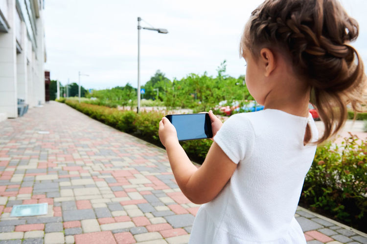 Little girl with a smartphone outdoors 5 Years Old Alone Beautiful Caucasian Cell Cellphone Child Childhood Concept Connection Daughter Device Entertainment Internet Leisure Little Girl Mobile Phone Outdoors Phone Small Girl Smartphone Street Summer Technology Wireless Technology