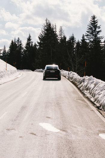 Car on snow covered landscape against sky