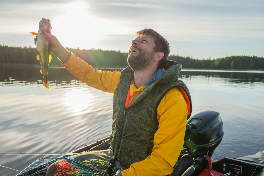 Handsome fisherman catched a haddock and looking to the sky Fish Fisherman Fishing Fishing Boat Karelia North Outboard Outboard Motor Tourism Tourist Yellow