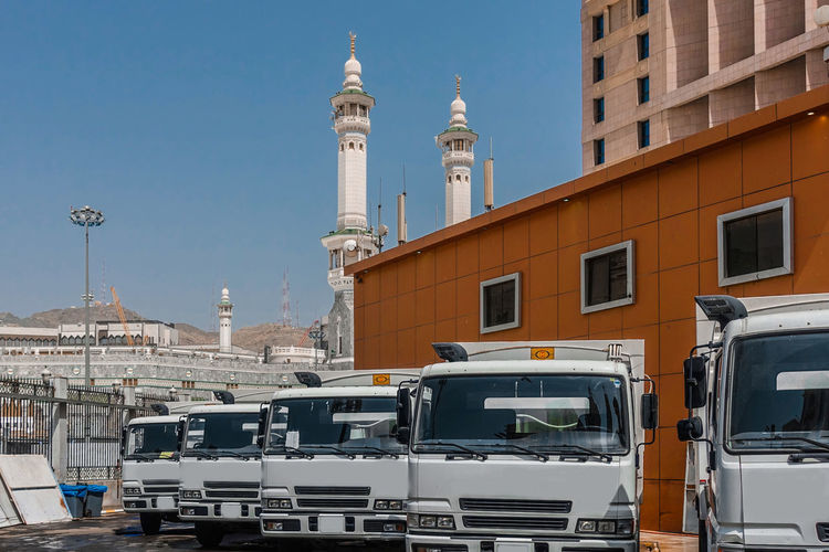 Trucks parking by building and mosque in city