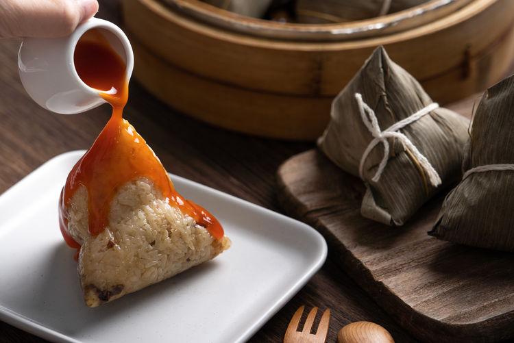 Eating zongzi rice dumpling for dragon boat festival celebration.