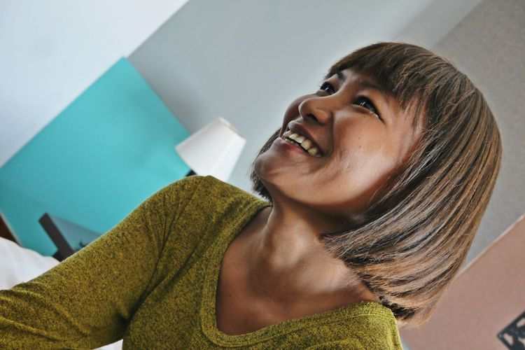Smiling woman with medium hair looking away at home