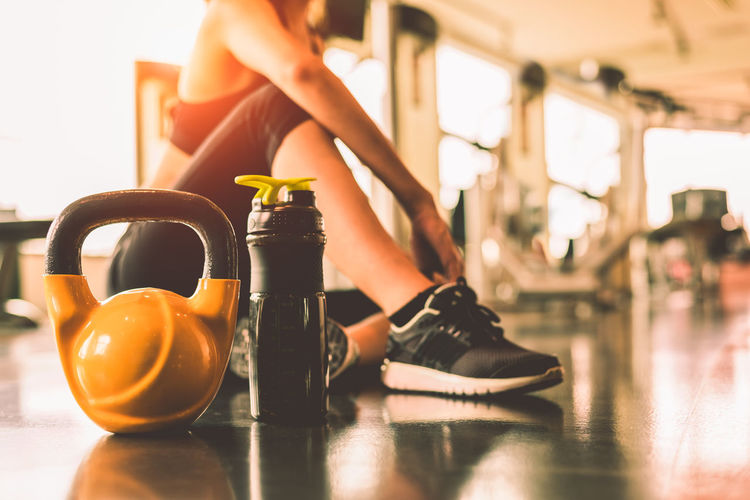 Low Section Of Woman With Kettlebell And Water Bottle Sitting In Gym
