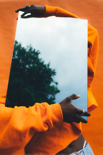 Close-up of hand against orange sky