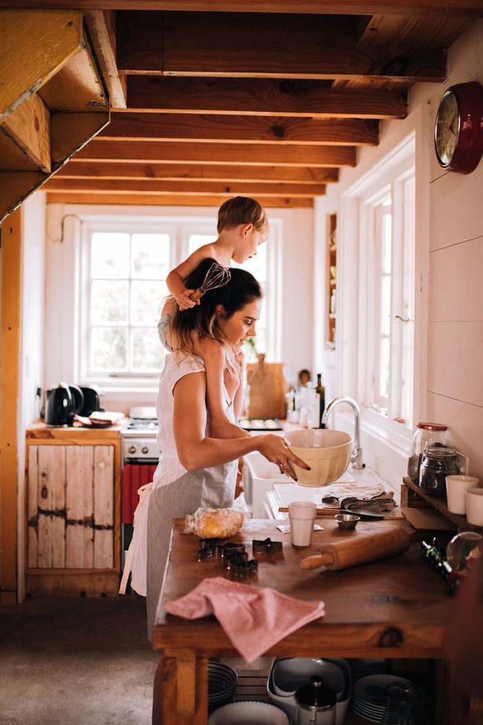 Mother carrying cute son on shoulders while standing in kitchen