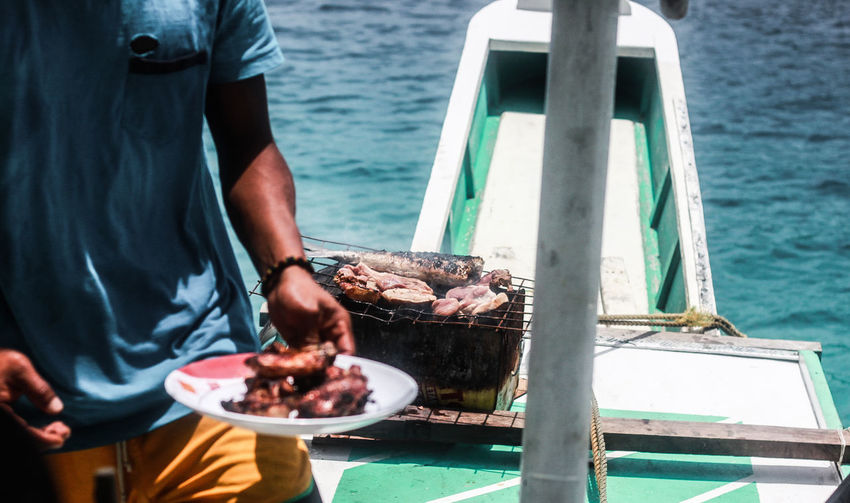 Midsection of man holding food plate while standing in boat sailing on sea