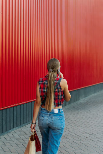 Rear view of woman standing against red wall