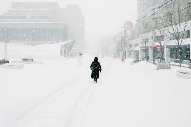 Rear view of man walking on snow covered buildings