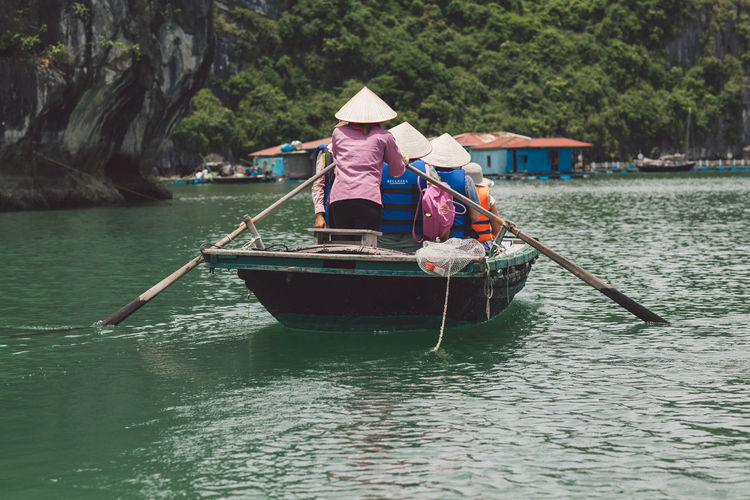 Rear view of people traveling in boat sailing over river