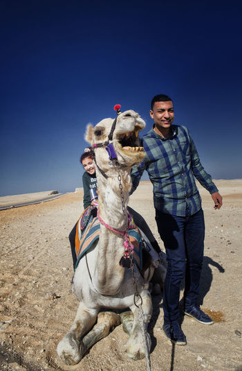 Portrait of people with camel in desert