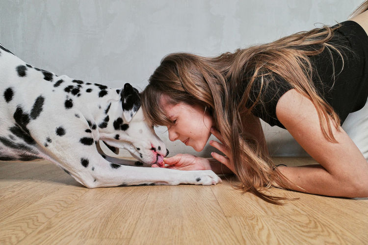 Side view of young woman with dog on hardwood floor