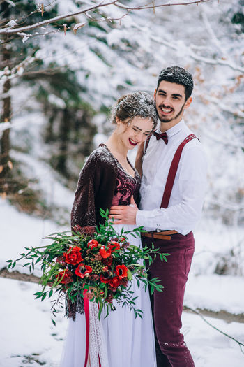 Young couple standing on snow covered plant