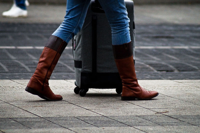 Low section of woman wearing boots walking on footpath