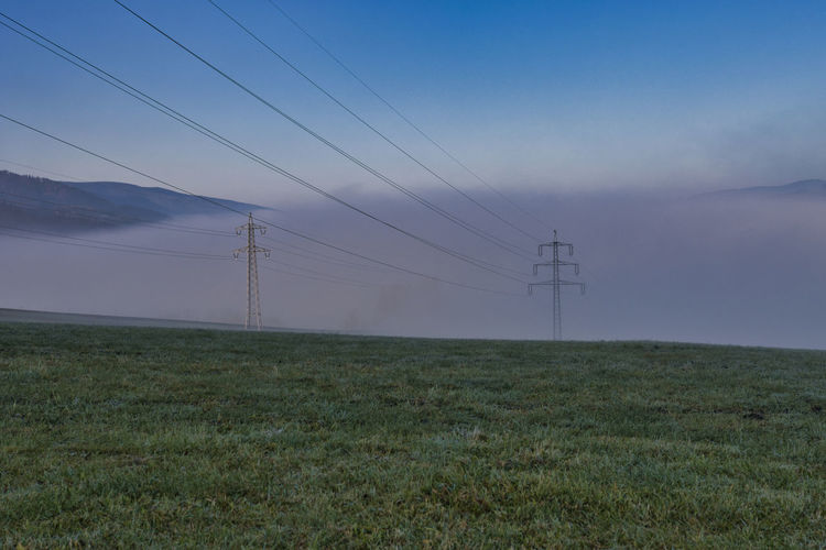 Electricity pylon on field against sky at dusk