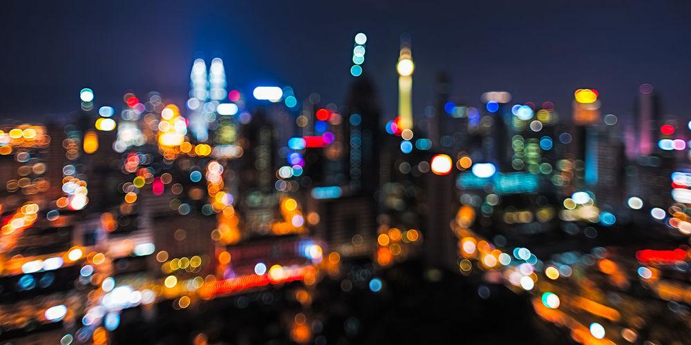 Defocuses image of illuminated petronas towers in city at night