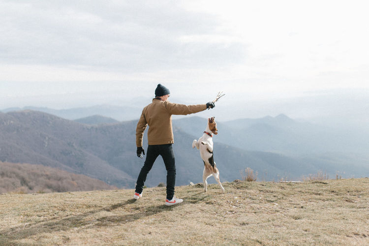 Rear View Of Man Playing With Dog While Standing On Mountain