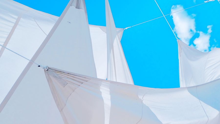 Low angle view of white sunshades against blue sky