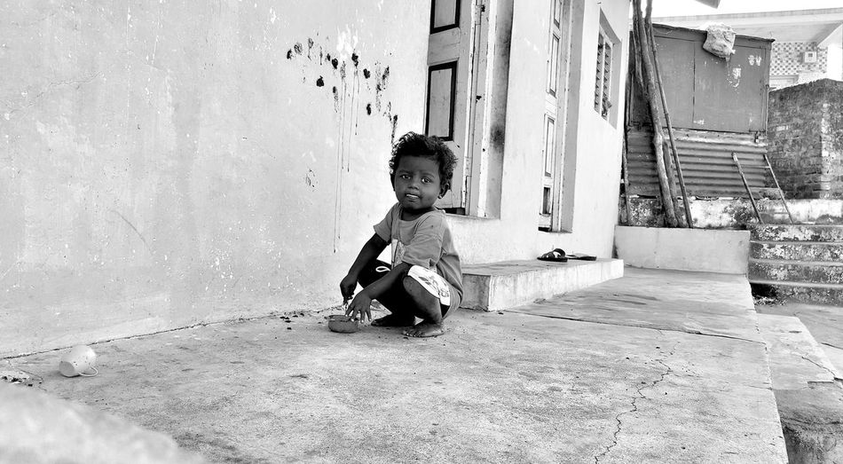 Portrait of boy crouching outside house
