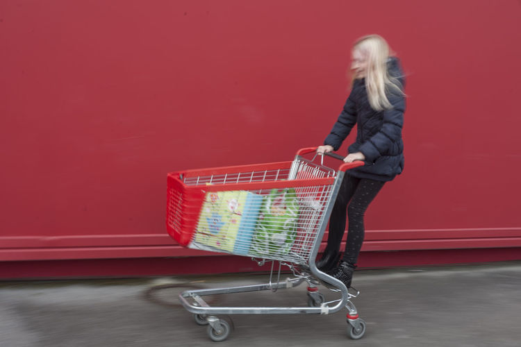 Cart Red Red Color Red Cart Full Length Shopping Cart Shopping One Person Consumerism Retail  Store Young Adult Colored Background Customer  Hair Pushing Supermarket Casual Clothing Blond Hair Buying Groceries Hairstyle Red Background Shopping Time Moving Streetwise Photography Analogue Sound