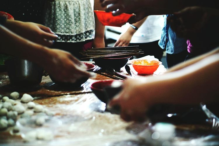 Midsection Of People Holding Bowls On Table