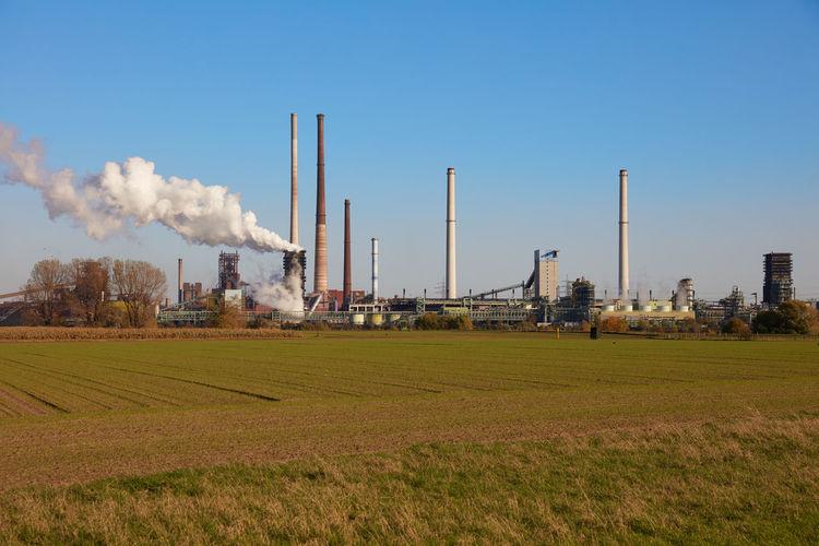 Smoke emitting from chimney on field against sky