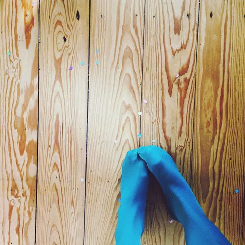 Low section of woman wearing blue socks while standing on floorboard