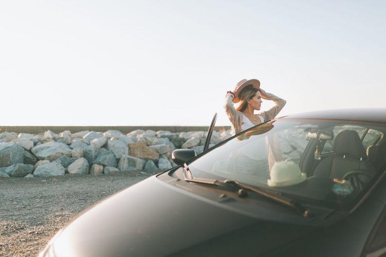 Woman on car against sky