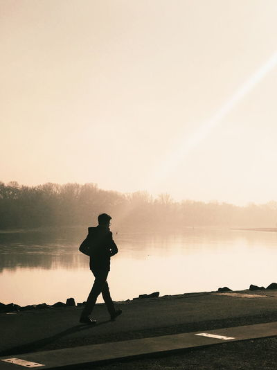 Silhouette man walking by lake against clear sky