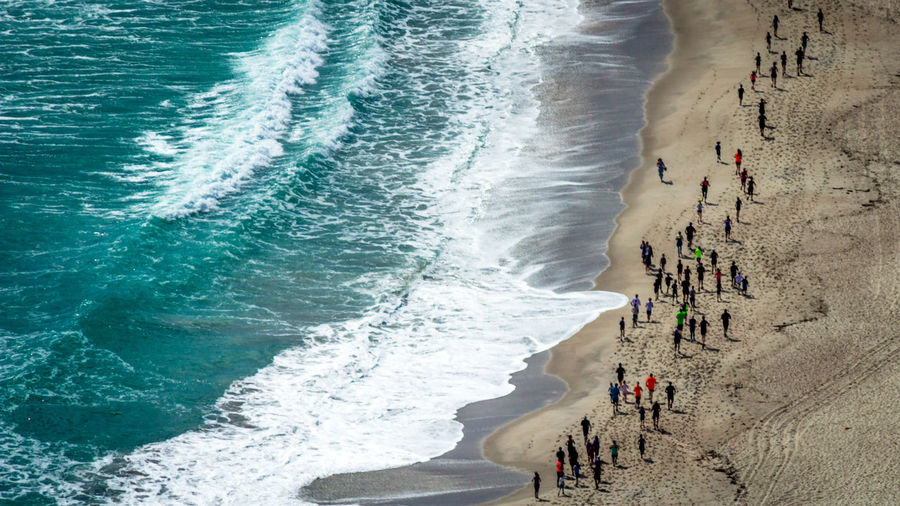 High Angle View Of People Running On Shore At Beach