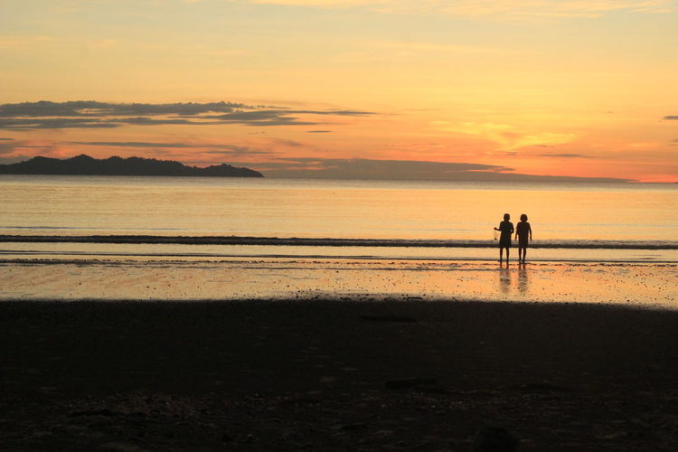 Silhouette children standing at beach against sky during sunset