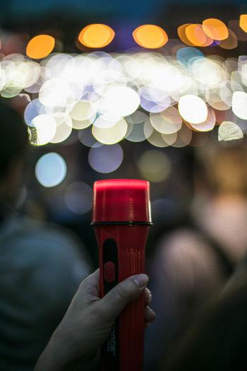 Cropped hand of protestor holding flashlight against illuminated light at night