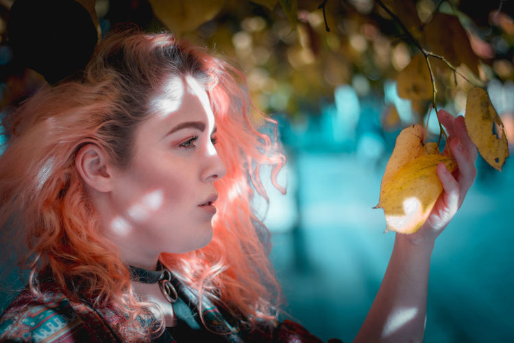 Close-up of thoughtful young woman with dyed hair touching autumn leaf