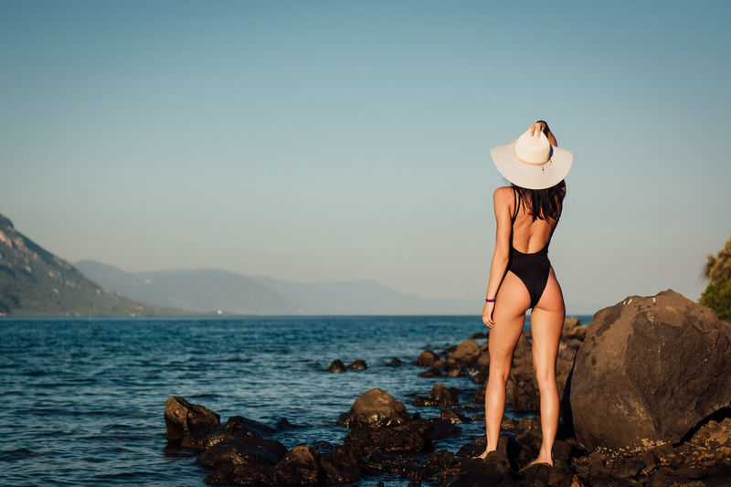Beauty In Nature Clothing Full Length Hat Holiday Land Leisure Activity Lifestyles Looking At View Nature One Person Outdoors Real People Rock Rock - Object Scenics - Nature Sea Sky Solid Sun Hat Vacations Water