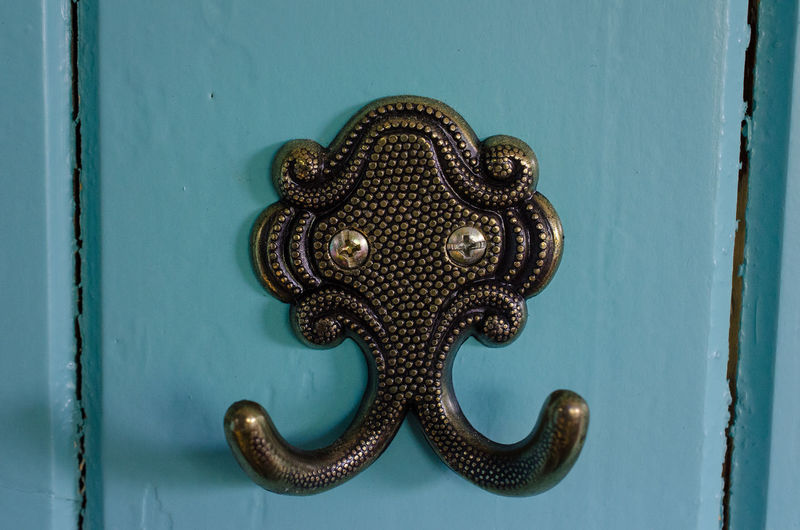 Close-up of ornate hooks on door