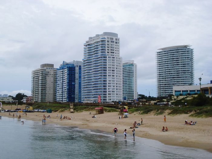 People on beach by buildings against sky