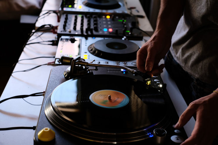 Cropped image of dj playing music from sound mixer at table
