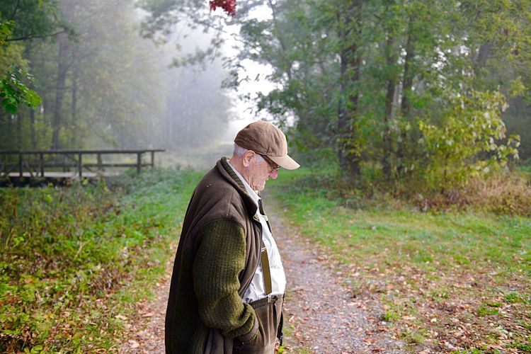 Profile view of senior man standing in forest