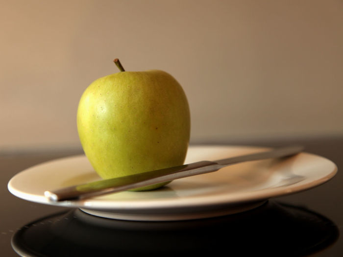 Close-Up Of Granny Smith Apple On Plate With Knife