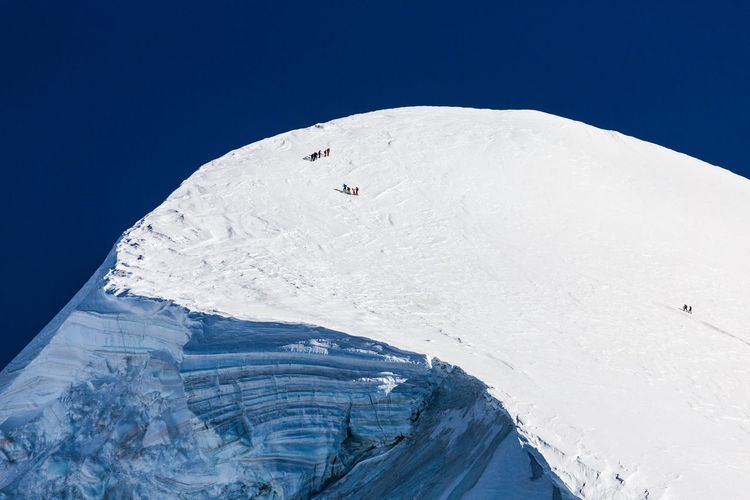 Aerial view of snowcapped mountain against blue sky